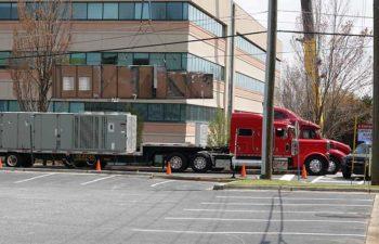 Trucks with industrial HVAC units. Big crane moving HVAC unit.