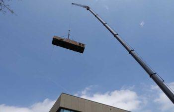 Big crane moving industrial HVAC unit.