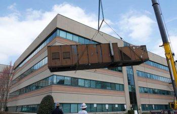 Big crane moving industrial HVAC. JS Thomas team at work.