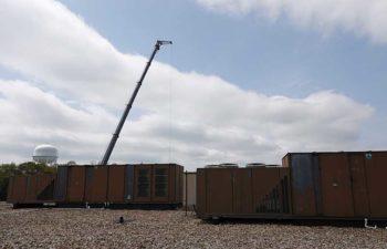 Big crane moving industrial HVAC.