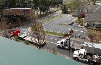 Big crane moving industrial HVAC. Trucks with HVAC units.