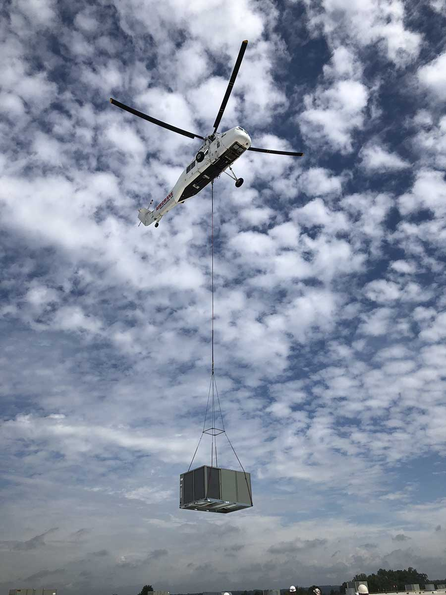JS Thomas Mechanical helicopter. Air crane transporting HVAC unit.